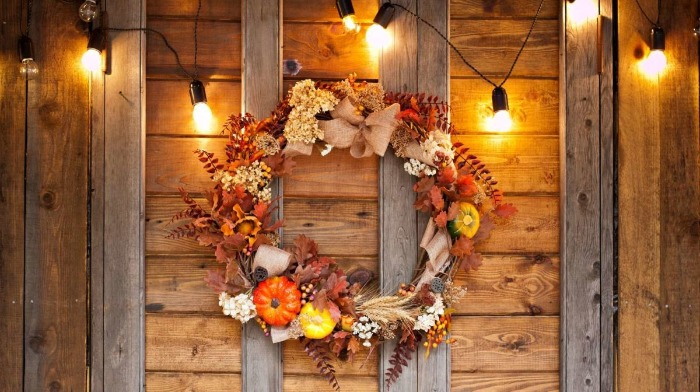 outdoor wreath with lights autumn themed leaves and pumpkins