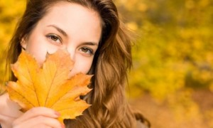 DIY Fall Wreathssmiling woman with a leave in front of her facr
