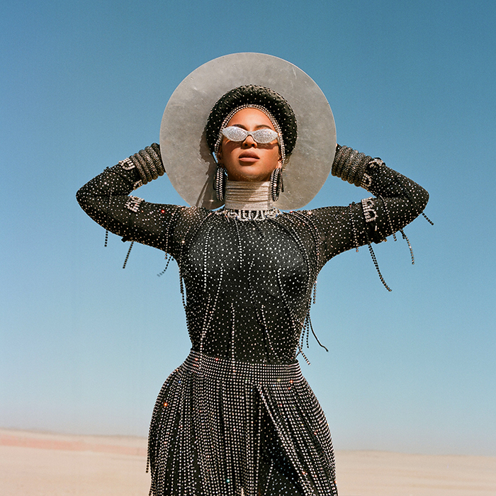 Halloween costume ideas black is king woman with a sparkly costume sun glasses and a hat