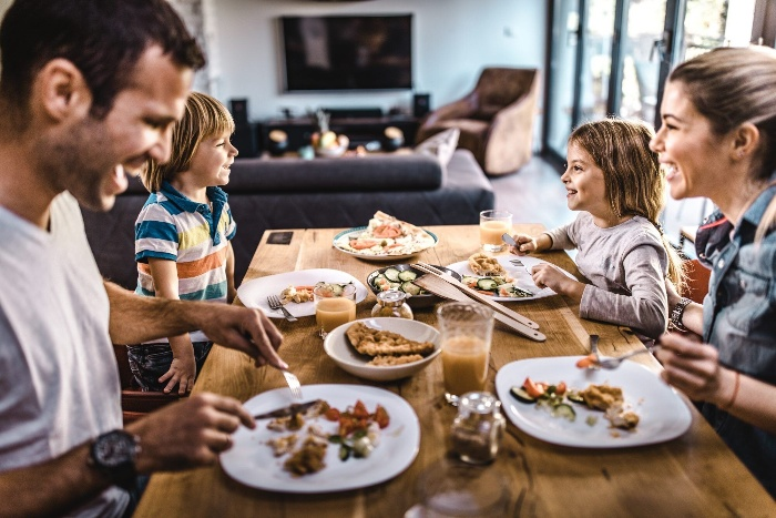 Thanksgiving celebration on a budget family of four on a dining table laughing and eating indoor activities