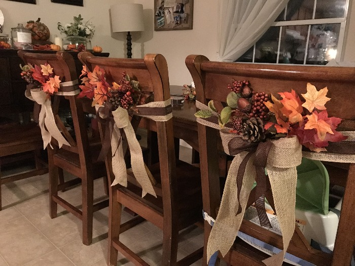 Thanksgiving decor fall themed chair decorations with foliage acorns and burlap ribbons