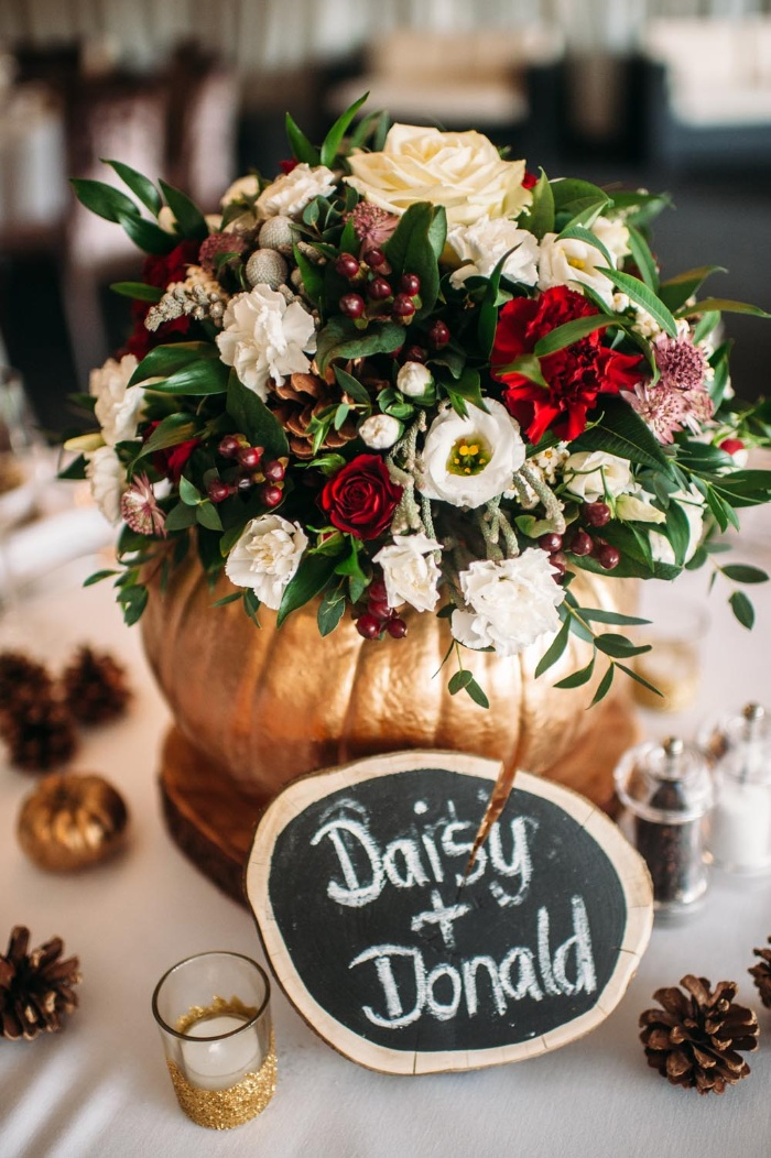 Thanksgiving color scheme golden pumpkin with a bouquet inside in white red and green
