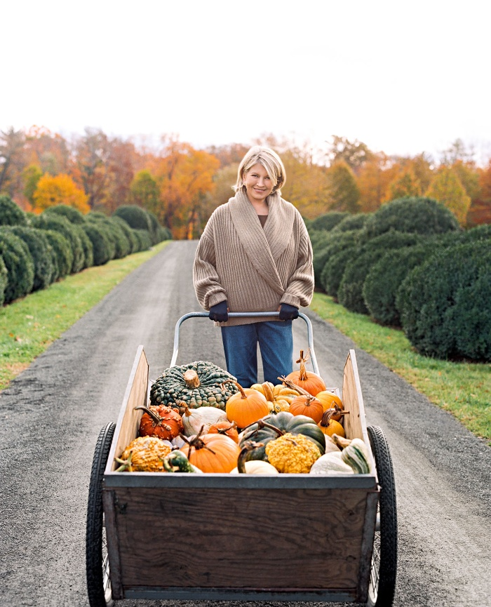 woman displaying fall harvest gourds and pumpkins in a beautiful yard