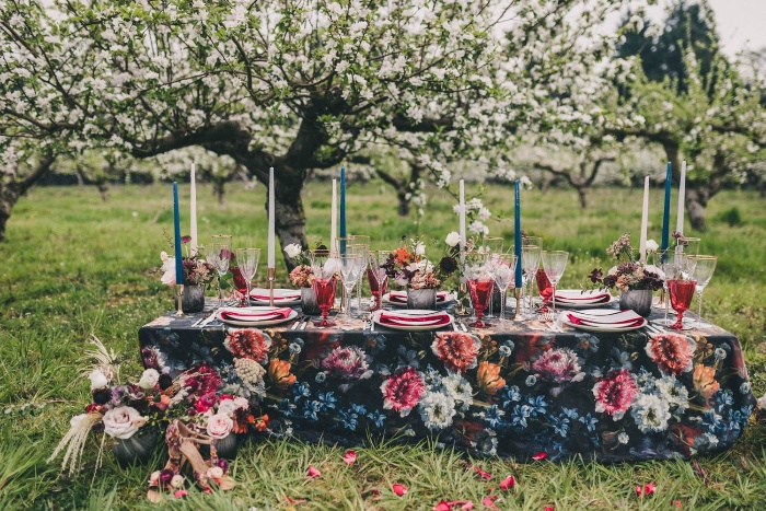outdoor wedding decor dark table with floral print on and tall candels