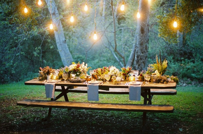 outdoor table thanksgiving themed wedding in a wood with outdoor lights