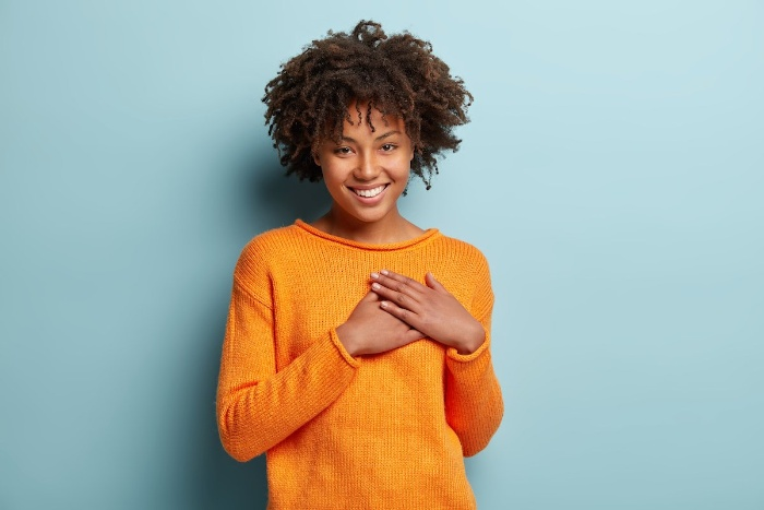 woman in yellow sweater smiling and holding her heart with two hands