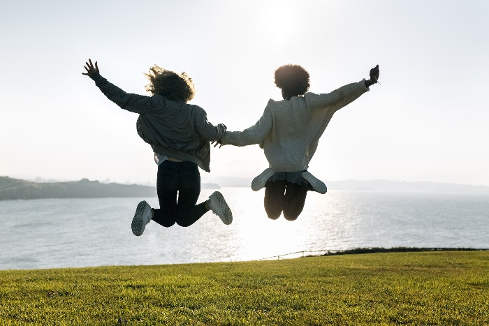 a couple holding hands and jumping in the air on a green field sea background