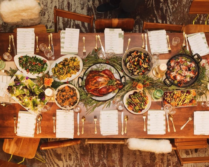 Thanksgiving celebration on a budget dining table from above with different dishes turkey at the center