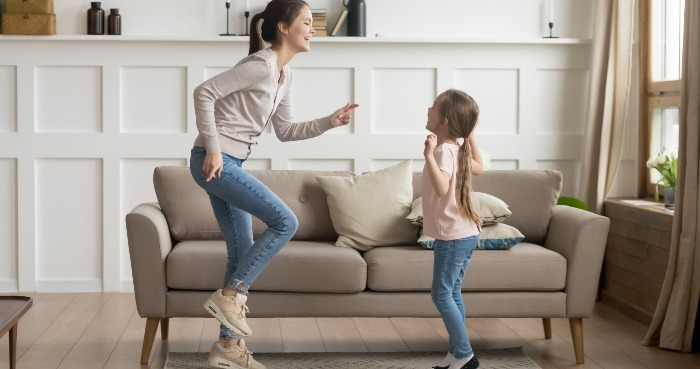 woman and little girl dancing and jumping indoors sofa and white wall in the background