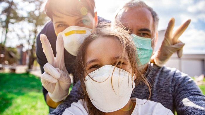family of three wearing masks mother father and daughter