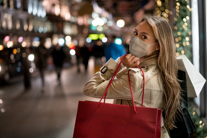 woman with a mask shopping for the holidays with a mask outdoors shopping street carrying a big read bag