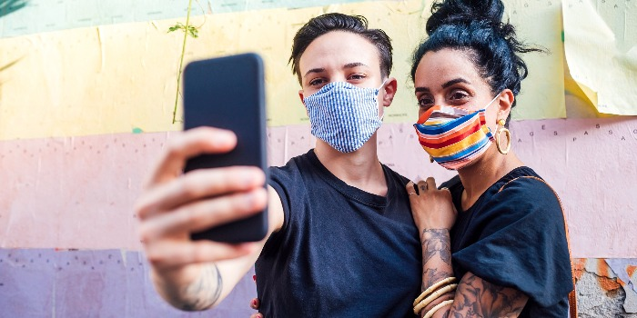 a girl and a boy with colorful masks taking a selfie in front of a wall