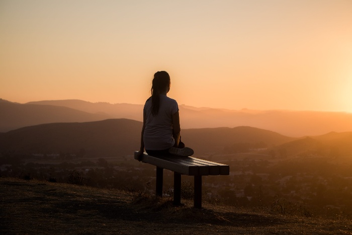 meditation for gratitude girl watching the sunset on a bench outdoors