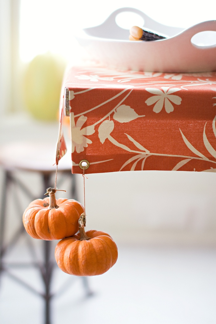Table decorated with mini pumpkins orange table cloth in a kitchen