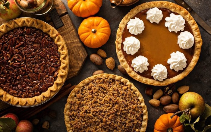 Thanksgiving treat different pumpkin pies with and without nuts with cream on a decorated table