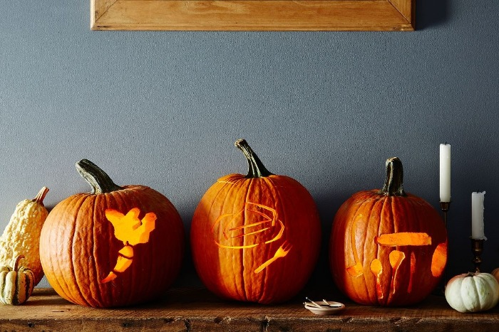 three carved pumpkins on a shelf gray wall in the background