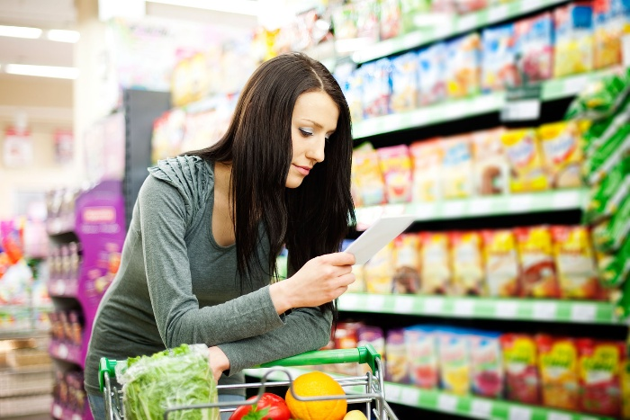 woman with dark hair looking at a shopping list in a supermarket