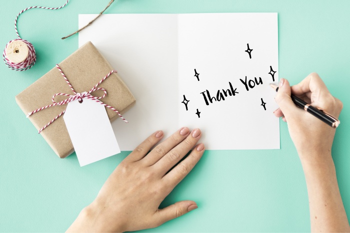 effect of gratitude person writing thank you card with a little wrapped gift