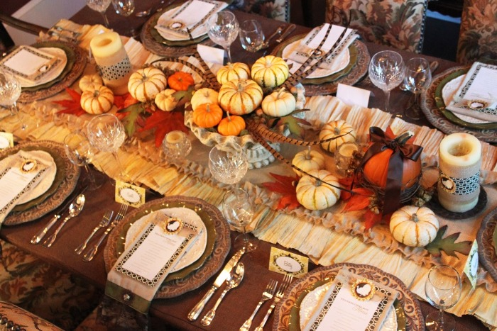 Thanksgiving decor table with abundant decorations pumpkins feather and fall motives