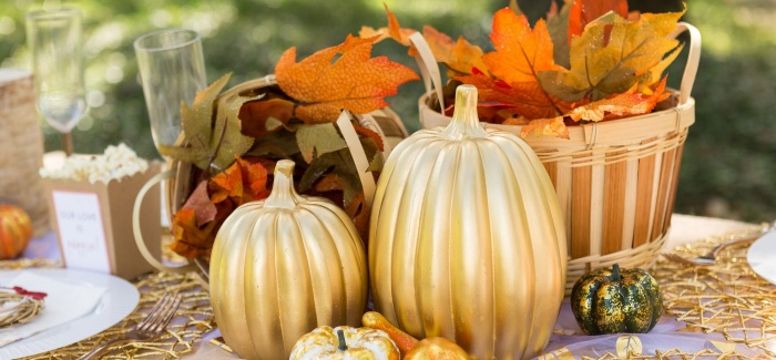thanksgiving themed table decor with golden pumpkins and foliage outdoor table setting