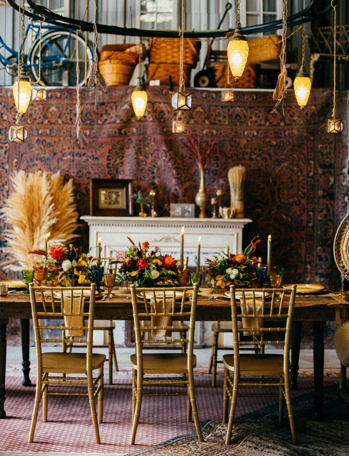 vintage wedding in rustic style table with golden chairs and floral centerpieces