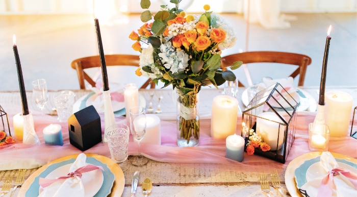 stylish wedding table with decorations in pink and light blue and tall dark candles