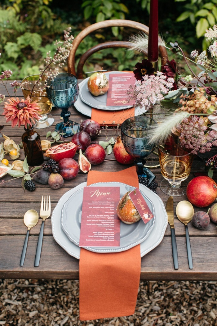 Thanksgiving themed wedding table decorated with fruits colorful glasses and flowers