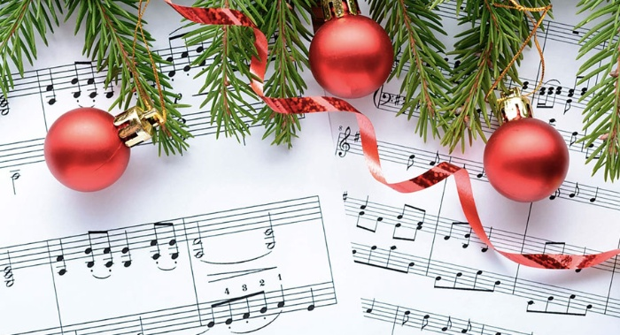 Christmas carol musical notes decorated with red baubles pine branches and a ribbon