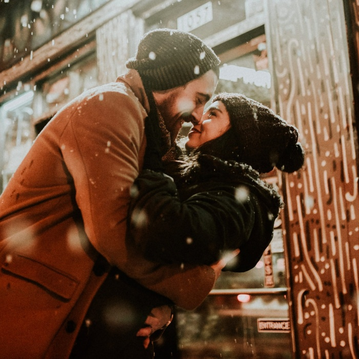 Couple outdoors dressed in winter clothes hugging and kissing in the snow