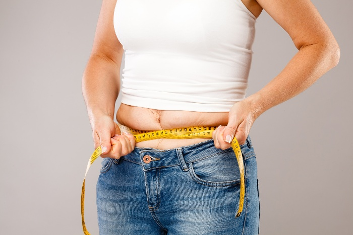 woman in jeans and white shirt measuring weigh gain with a meter