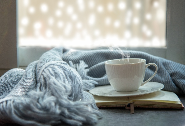 Holiday season white cup with light blue blanket in front of a window