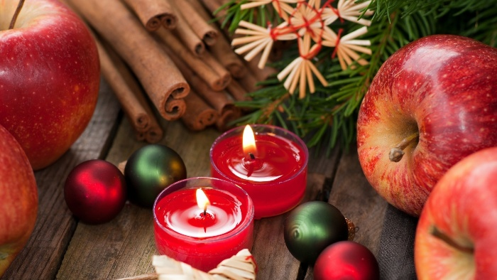 Christmas arrangement with apples cinnamon candles and christmas decorations