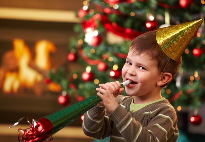 child with a golden party hat playing with a red and green paper trumpet