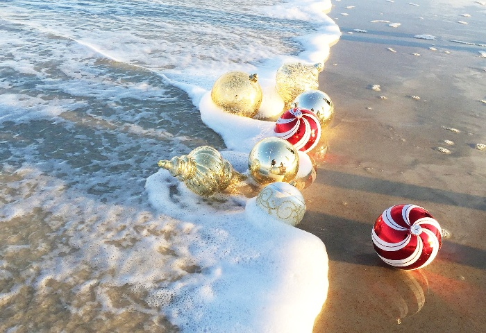 Christmas ornaments and baubles on the beach washed by the waves