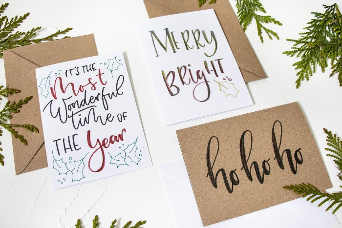 christmas cards with beautiful calligraphy on a white table