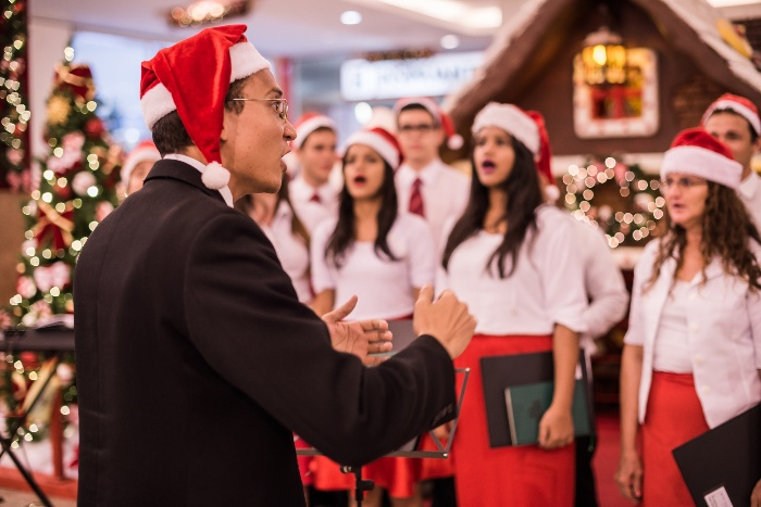 christmas choir performance singers dressed in white and red and a conductor with a red hat
