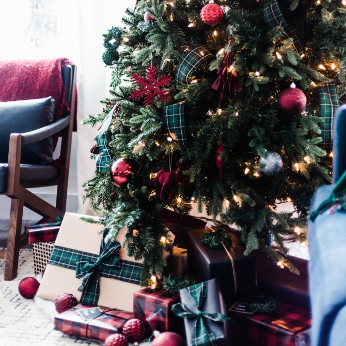 christmas decorations tree decorated in green and red with presents under it and a reading chair