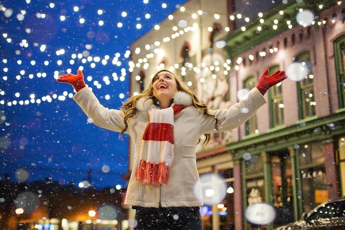 christmas in czech republic woman in a jacket and scarf with hands spread outdoors in the snow