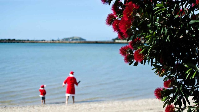christmas in new zealand Santa and his helper on a beach in their costumes