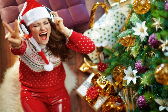christmas songs woman with headphones under a christmas tree listening to her favourite songs