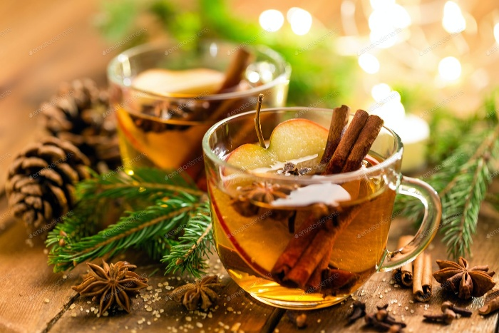 christmas tea in glass cups with cinnamon sticks star anise and apple slices