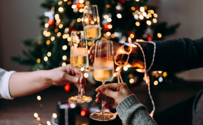 christmas toast with champagne in front of a christmas tree
