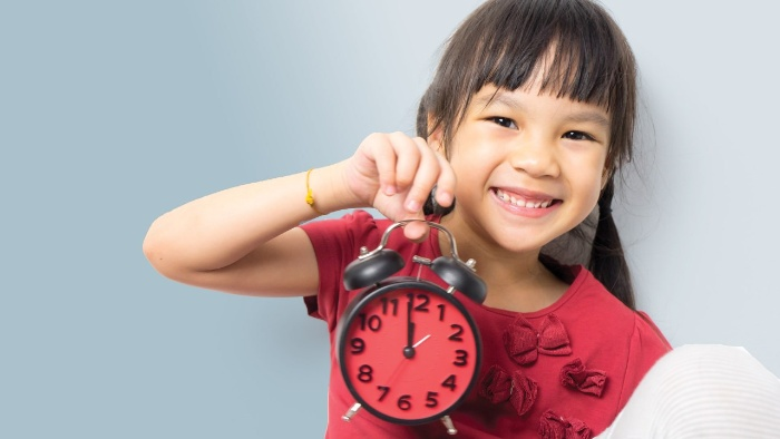 little girl with red shirt holding a red clock in her hand