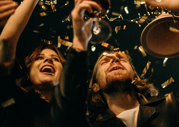 couple cheers at new year's eve party with confetti in flying in the air
