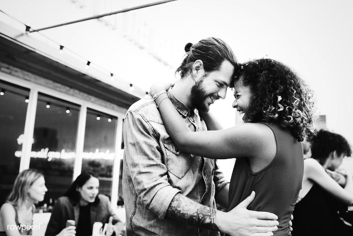 couple dancing at a party with foreheads together in a dance