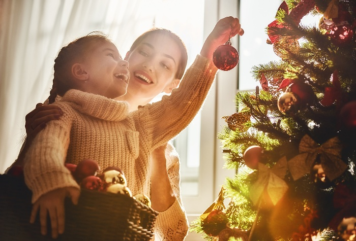 mother and daughter decorating the christmas tree in front of a window
