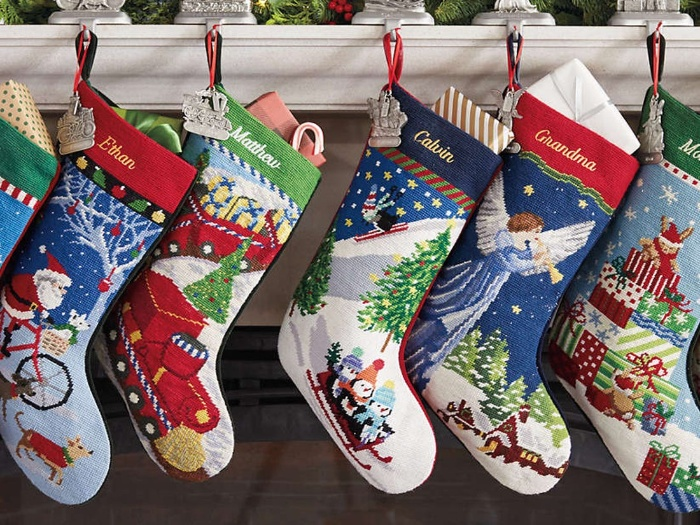 cute colorful christmas stockings hanging from a mantel above a fireplace