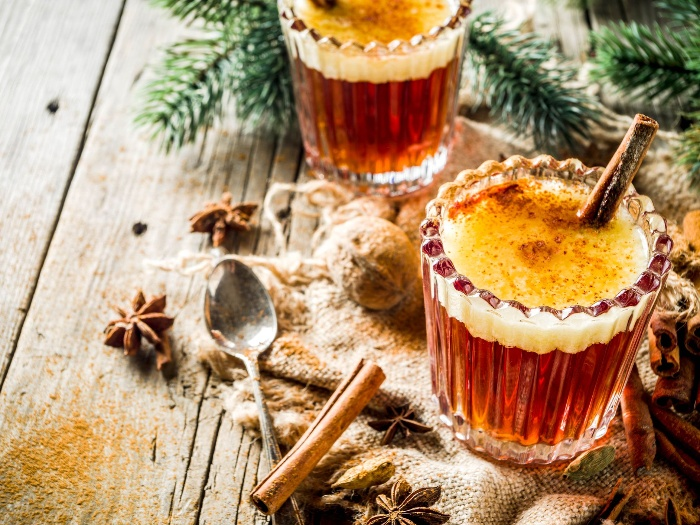 two warm drinks with cinnamon on a table decorated with winter spices