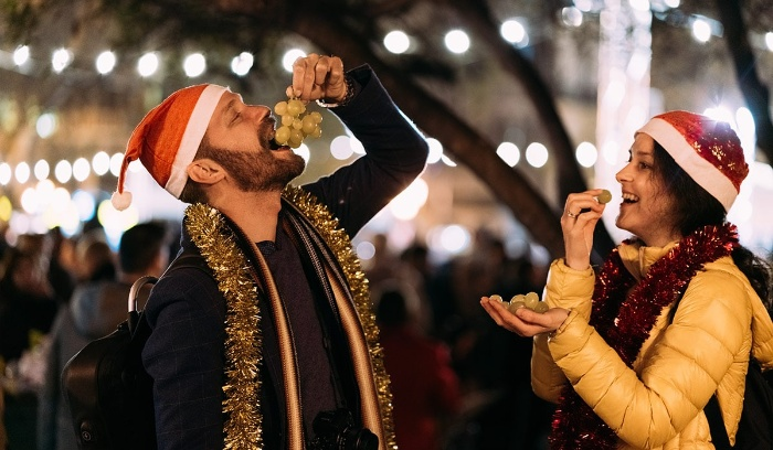 couple eating grapes together at new year's eve outdoor market