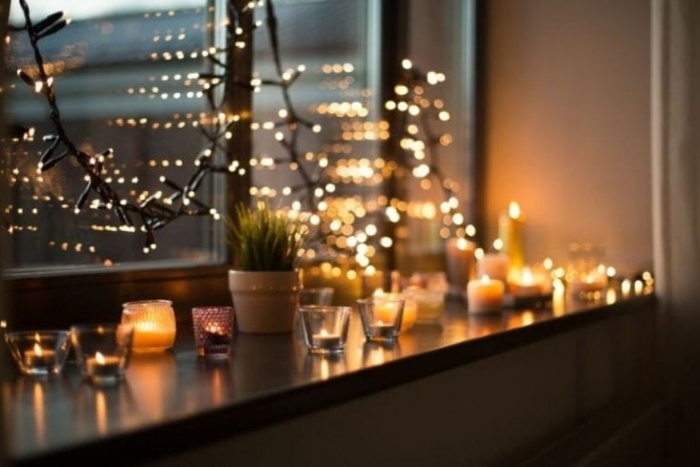 fairy lights and candles arranged on a window sill